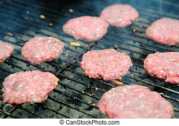 Raw Hamburgers On The Grill - Uncooked hamburger patties...