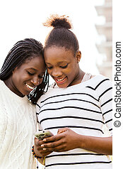 African teen girls texting on smart phone. - Close up...