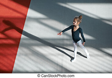 Girl practicing rhythmic gymnastics in gym - Girl practicing...