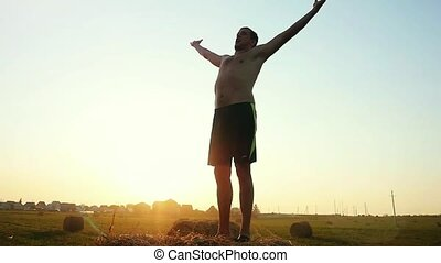 Young man with naked torso raises his hands in a field in...
