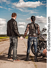 Bikers couple - Biker man and girl stands on the road and...
