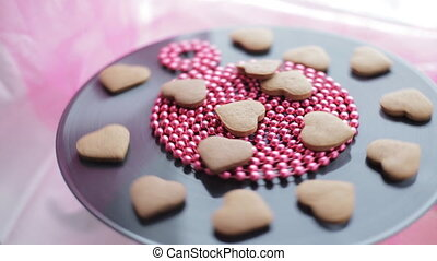 Heart-shaped gingerbread cookies rotating on vinyl record -...
