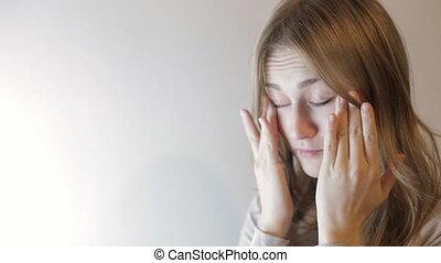 Blonde woman rubs her eyes