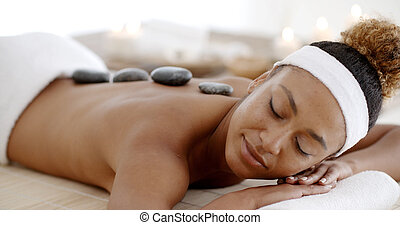 Woman Getting Hot Stones Massage At Spa