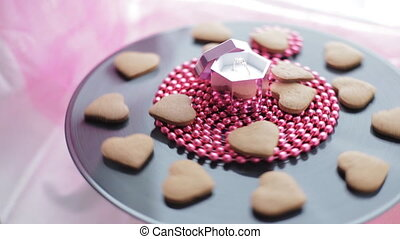 Wedding ring in pink box with gingerbread cookies - rotating...