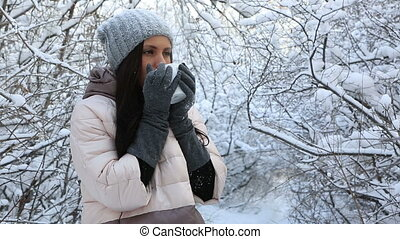 Beautiful happy girl warms up with hot tea. Snow covered trees in winter park.