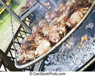roasted pork knuckle on brazier in country fair - roasted...