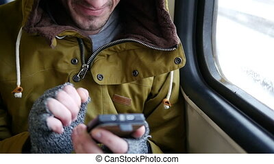 man reading text messages on a mobile on a tube train HD