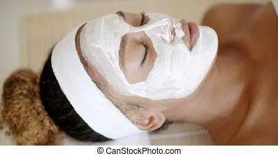 Woman With Facial Mask At Salon - Therapist applying a face...