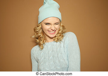 Gorgeous young woman with blond ringlets in a green knitted...