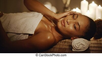 Woman Lying On Massage Table And Touching Her Face - Young...
