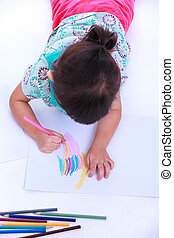 Top view Child lie on the floor and drawing on paper On...
