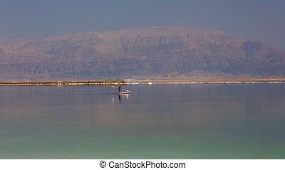 man floats on the board in Dead Sea