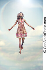 Young woman flying up. Soft colors.