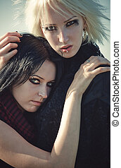 Two goth women concept portrait. Soft yellow and blue tint.