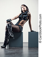 Young sexy woman sitting on a cube