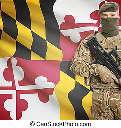Soldier holding machine gun with USA state flag on...