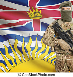 Soldier holding machine gun with Canadian province flag on...