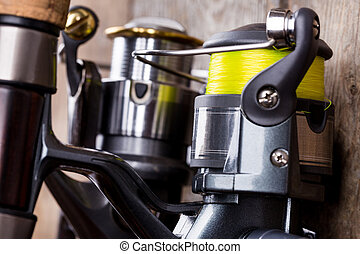 closeup fishing reel on wooden board background - closeup...