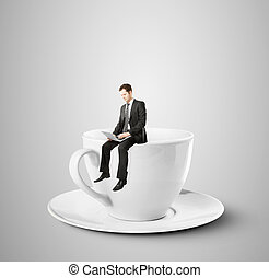businessman sitting on coffee cup - businessman sitting with...