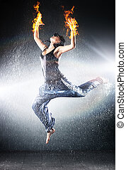Young woman modern dance. Water studio photo and fire...