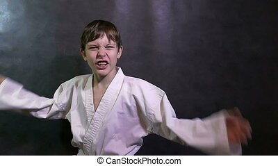 Karate boy angry kid shouts waving his arms defeat