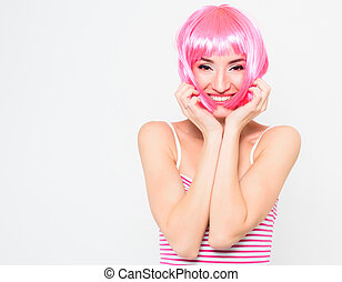 Cheerful young woman in pink wig and posing on white background