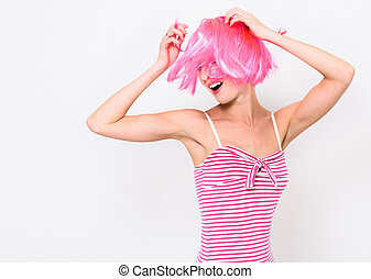Cheerful young woman in pink wig and dancing on white background