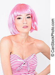 Cheerful young woman in pink wig posing on white background