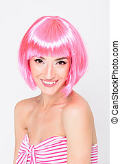 Smiling young woman in pink wig posing on white background