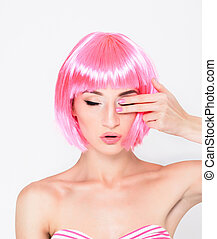 young woman in pink wig posing on white background