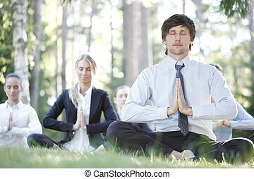 Business people practicing yoga in park