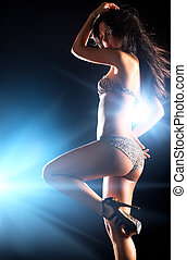 Young sexy dancing woman. On dark background with flashes...