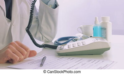 Male doctor dialing a phone in a medical office - Doctor...