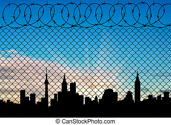 Silhouette of the city behind a fence topped - Concept of a...