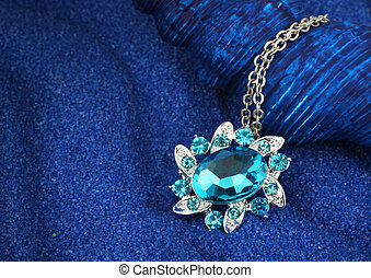 Jewelry pendant with gems on dark blue background with copy-space