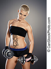 girl with dumbbells - Muscular young woman with beautiful...