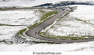 Cyclist goes downhill along a mountain road in a snowy landscape