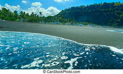Boats on the beach of black sand on the island of Bali in Indonesia in sunny summer day