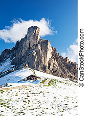 Mountain hut and Nuvolau peak after a summer snowfall. Passo...