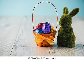 Easter eggs in a basket with a bunny on a white table