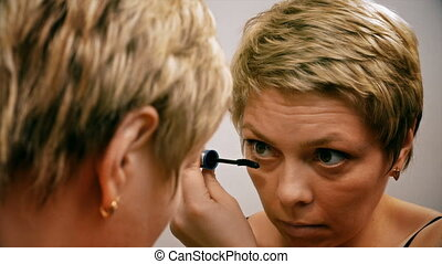Pretty blond woman applying mascara make-up on her eyelashes...