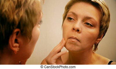Woman applies make-up concealer foundation cream - Beautiful...