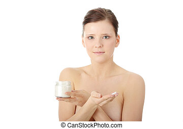 Woman applying moisturizer cream on face. Close-up fresh...
