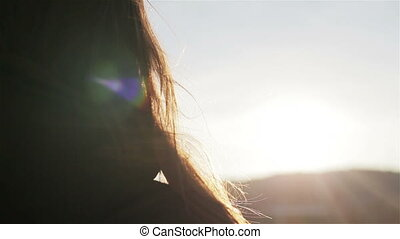 Young woman touch her hair at wind