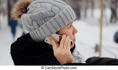 Girl in the park in winter on the phone and smiling outdoor