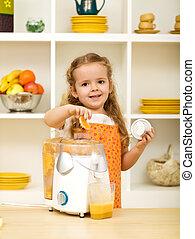 Little girl making fresh fruit juice