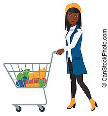 Customer with trolley. - An african-american woman pushing a...