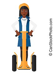 Woman riding on segway - An african-american woman riding on...