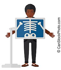 Patient during x-ray procedure - An african-american patient...